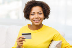 Happy african woman with credit or debit card. People, bank, shopping and e-money concept - happy african american young woman sitting on sofa with credit or Stock Image