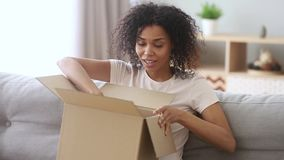 Happy african woman customer open cardboard box sitting on sofa stock video