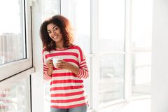Happy african woman drinking coffee near the window. And looking at the camera Stock Photo