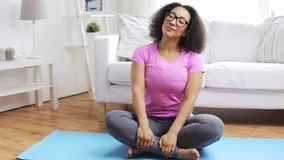 Happy african woman exercising on mat at home