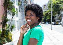 Happy african woman in a green shirt in the city Stock Photos
