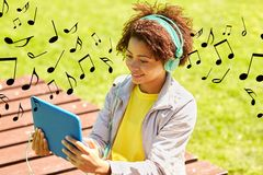 Happy african woman in headphones with tablet pc Stock Photo