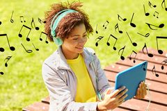 Happy african woman in headphones with tablet pc Royalty Free Stock Photography