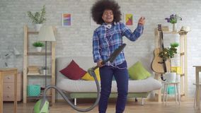 Happy african woman with an afro hairstyle dancing with a mop from a vacuum cleaner in living room slow mo. Happy african woman housewife with an afro hairstyle stock video footage