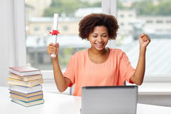 Happy african woman with laptop, books and diploma Royalty Free Stock Photos