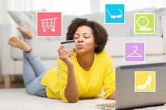 Happy african woman with laptop and credit card Stock Photo