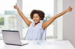 Happy african woman with laptop at office stock image