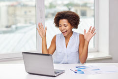 Happy african woman with laptop at office Stock Photo