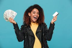 Happy african woman in leather jacket holding money. And credit card while looking at the camera over blue background Royalty Free Stock Photo