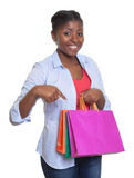 Happy african woman pointing to her shopping bags Stock Photography