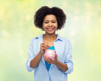 Happy african woman putting coin into piggy bank Stock Images