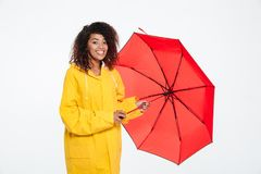 Happy african woman in raincoat posing with umbrella Stock Photography