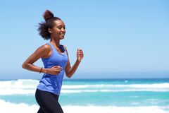 Happy african woman running on the beach Stock Photo