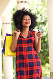 Happy african woman with shopping bags and cellphone outside Stock Photo