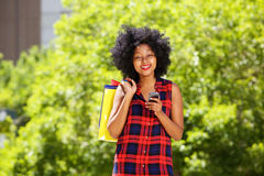 Happy african woman with shopping bags and cellphone outside Royalty Free Stock Photo