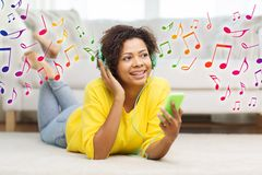 Happy african woman with smartphone and headphones Stock Images