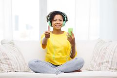 Happy african woman with smartphone and headphones Stock Image