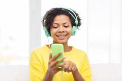 Happy african woman with smartphone and headphones Stock Photos