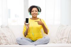 Happy african woman with smartphone and headphones Royalty Free Stock Photos