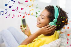 Happy african woman with smartphone and headphones Royalty Free Stock Photo