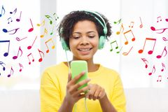 Happy african woman with smartphone and headphones Stock Photography