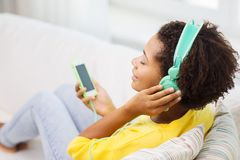 Happy african woman with smartphone and headphones Royalty Free Stock Photography
