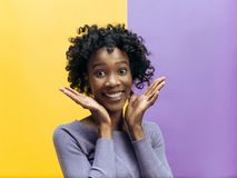 The happy african woman standing and smiling against gray background. stock photos