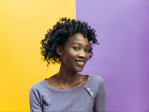 The happy african woman standing and smiling against gray background. stock images