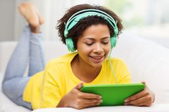Happy african woman with tablet pc and headphones Stock Image