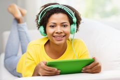 Happy african woman with tablet pc and headphones Royalty Free Stock Image