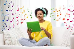 Happy african woman with tablet pc and headphones Royalty Free Stock Images