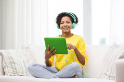 Happy african woman with tablet pc and headphones Stock Photography