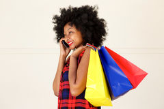 Happy african woman talking on phone with shopping bags Royalty Free Stock Photography