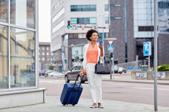 Happy african woman with travel bag and smartphone Stock Photo