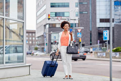 Happy african woman with travel bag and smartphone Stock Photos