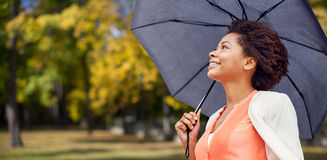 Happy african woman with umbrella in autumn park Royalty Free Stock Images