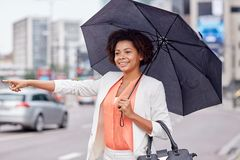 Happy african woman with umbrella catching taxi Stock Images
