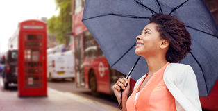 Happy african woman with umbrella in london city. Weather, travel, tourism, citylife and people concept - young smiling african american woman with umbrella over Stock Image