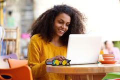 Happy african woman using laptop at cafe Stock Photos