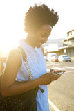 Happy african woman using mobile phone outdoors in the city Royalty Free Stock Photo
