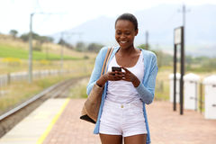 Happy african woman using mobile phone at railway station Royalty Free Stock Photo