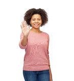 Happy african woman waving hand over white. People, race, ethnicity and gesture concept - happy african american young woman waving hand over white Royalty Free Stock Images