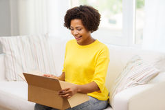 Happy african young woman with parcel box at home Royalty Free Stock Images