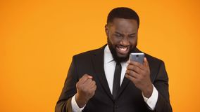Happy afro-american businessman holding smartphone and making yes gesture, win. Stock footage stock video footage