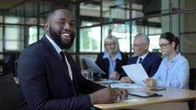 Happy afro-american businessman smiling camera sitting office table, career stock video footage