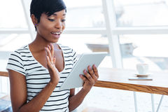 Happy afro american businesswoman holding tablet computer and waving Royalty Free Stock Image