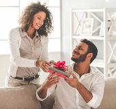 Happy Afro American couple. At home. Beautiful girl is giving a gift box to her boyfriend Royalty Free Stock Photo