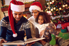 Happy afro American family read a book at fireplace on Christmas. Eve. Family with child celebrating Xmas stock image