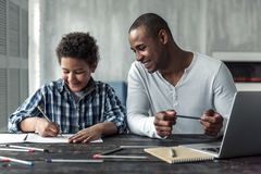 Father and son. Happy Afro American father and son in casual clothes are drawing and smiling while sitting at the table at home royalty free stock photos