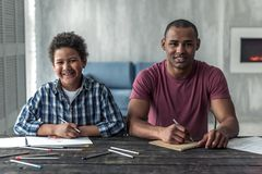 Father and son. Happy Afro American father and son in casual clothes are looking at camera and smiling while drawing at the table at home royalty free stock photos